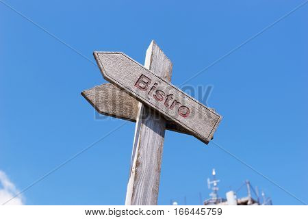 Text Bistro on a wooden sign with blue sky in the background