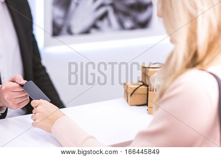 Receptionist at beauty salon is giving black plastic card to a client. Focus on hands