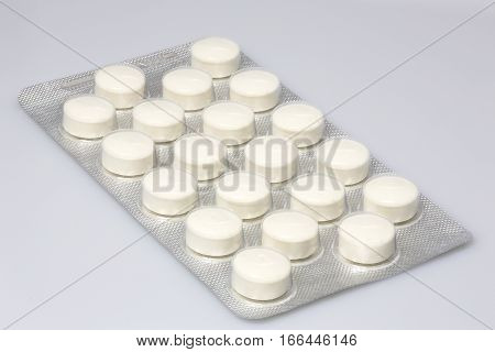 Group of large white tablets in packaging closeup