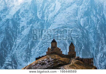 Caucasus mountains ancient Gergeti Trinity church Tsminda Sameba against the glacier near mount Kazbek landmark of Georgia