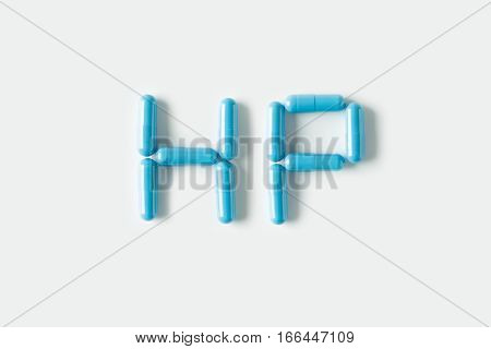 Blue Pills Capsules In Shape Of Word Hp. Life Concept Isolated.
