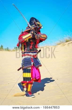 Men in samurai armour with sword running on sand