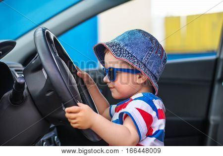 Cute little boy with glasses sitting in the car and keeps the wheel