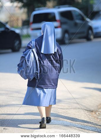 Nun With A Blue Suit And Small Backpack