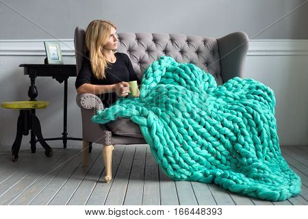 Cozy composition closeup of woman with merino wool plaid having a rest warm and comfortable atmosphere.