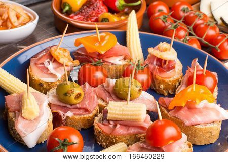 Spanish tapas sandwiches with olives ham and tomatoes