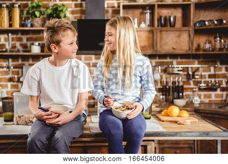 Brother and sister have breakfast sitting on the table in kitchen
