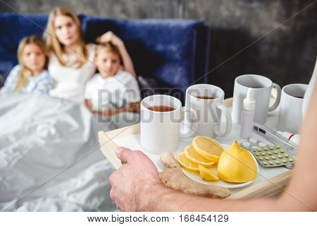 Man brings tray with tea and medicine for his wife and children lying on bed