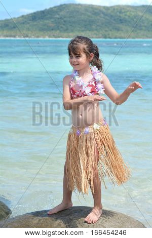 Young girl dressed up as a hula girl dance against blue lagoon and Island in the Pacific Ocean. Travel holiday vacation concept. Real people copy space