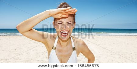 Cheerful Woman In White Swimsuit At Sandy Beach On Sunny Day