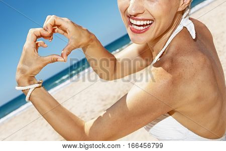 Woman In Swimsuit Showing Heart Shaped Hands At Sandy Beach