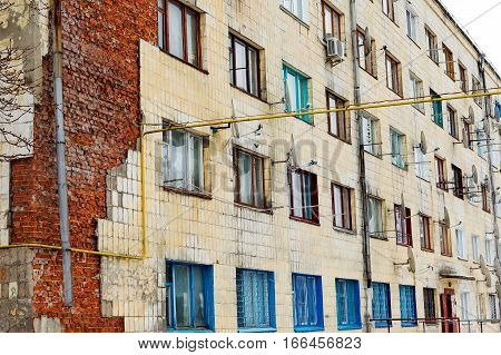 Old High-rise Building With Broken Windows, Crumbling Walls Covered With Cracks And Scratches
