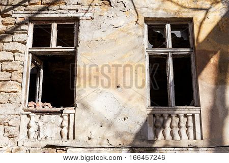 Old Building Falling Apart With Broken Windows, Walls Covered With Cracks And Scratches
