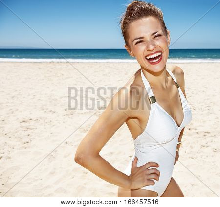 Portrait Of Smiling Woman In White Swimsuit At Sandy Beach