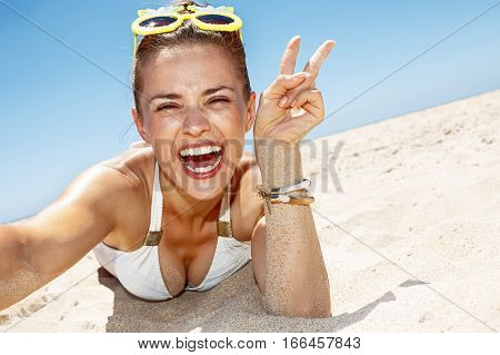 Woman Taking Selfies And Showing Victory Gesture At Sandy Beach
