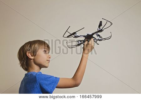 Little kid playing with drone. Boy holding quadcopter in his hand, preparing to fly. Technology, leisure toys concept