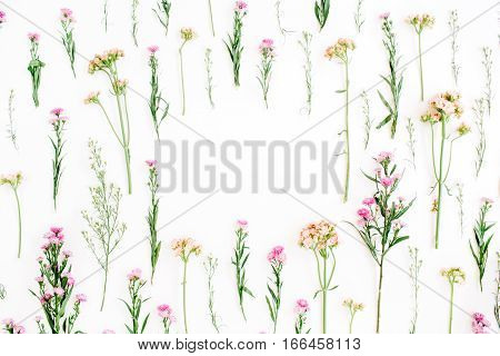 Frame with colorful wildflowers green leaves branches on white background. Flat lay top view. Valentine's background