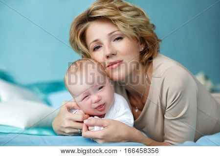 Portrait on a blue background young beautiful happy mother with blond hair and her thick sweet cute newborn baby boy playing and lying on a blue blanket on the bed at home, the mother in a beige dress hugs baby, baby in white overalls