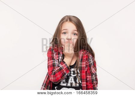 Shocked kid girl over white background. Scared and sad little girl holding hand over mouth