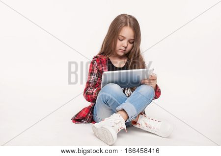 education, school, technology concept - little student girl with tablet pc doing homework over white background. Full length body portrait of kid holding a tablet device