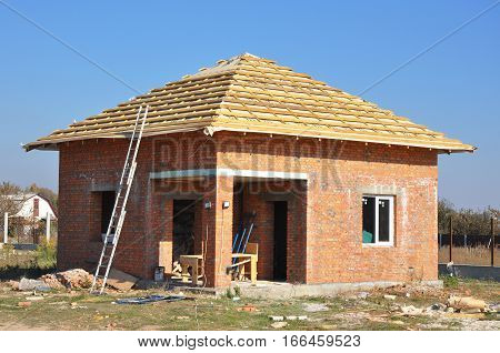 Building sauna or bathhouse from brick with roofing construction. House construction site.