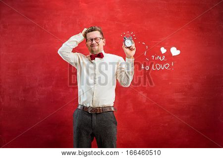 The young funny man with abstract clock on red studio background. Concept - time to congratulate. The happy Valentine's Day concept