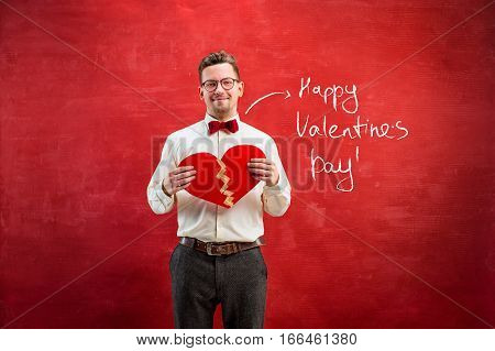 The young funny man with abstract broken and glued heart on red studio background. Concept - unhappy and happy love. The happy Valentine's Day concept