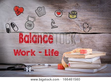 Work Life Balance Concept. Stack of books and a stethoscope on a wooden background.