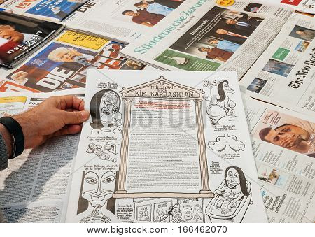 PARIS FRANCE - JAN 21 2017: Philosophy of Kim Kardashian in Charlie Hebdo above major international newspaper journalism featuring headlines with Donald Trump inauguration as the 45th President of the United States in Washington D.C
