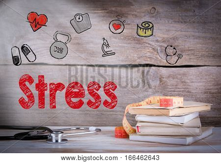 Stress Concept. Stack of books and a stethoscope on a wooden background.
