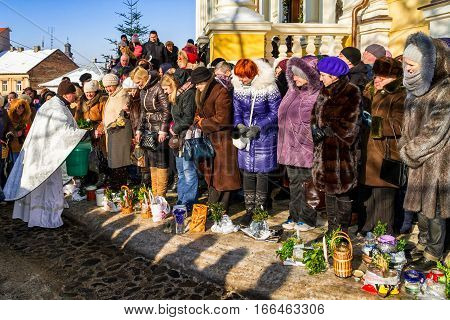 Uzhgorod Ukraine - January 19 2017: Greek-Catholic priest (L) conducts a ceremony blessing parishioners during the celebration of the Epiphany Day. Epiphany Day completes the Christmas-New Year festivities cycle in Ukraine.