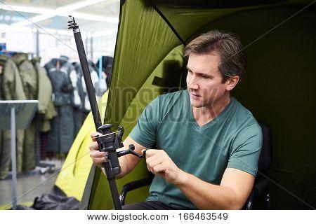 Man Chooses Fishing Rod In Shop