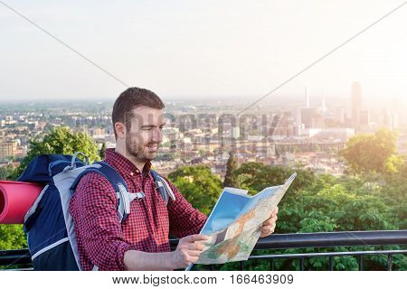 Tourist backpacker with map searching place in the city
