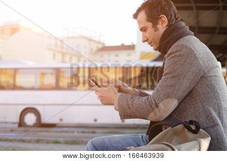 Man waiting at the bus station and looking at his smart-phone