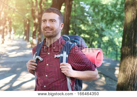 Backpack man smiling during an exploration in the forest