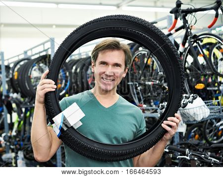 Man Chooses Tire To Bike In Sports Shop