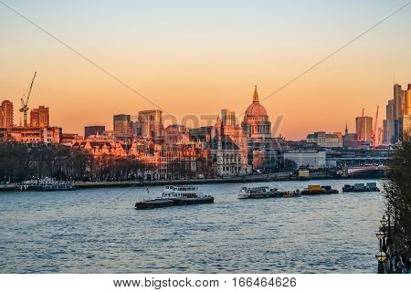 London skyline view from a bridge over the Thames looking towards the City. Bright winter's afternoon sunset showing St. Pauls and the River Thames.