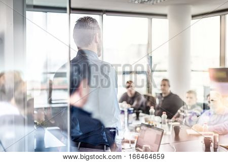 Business man making a presentation at office. Business executive delivering a presentation to his colleagues during meeting or in-house workshop. Rear view. Business and entrepreneurship.