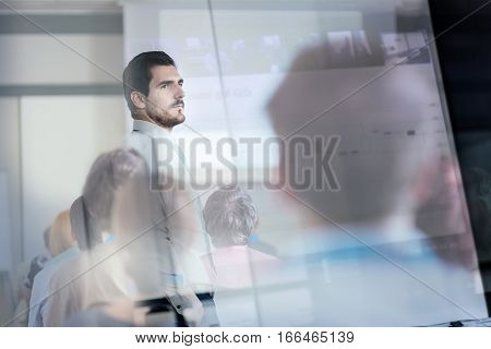 Business man making a presentation in front of whiteboard. Business executive delivering a presentation to his colleagues during meeting or in-house business training. View through glass.