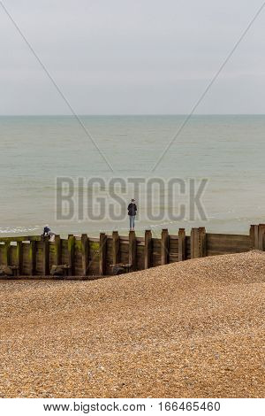 Youth standing on a groyne on the beach. Shot taken in early summer at Eastbourne of a young land balancing on this wooden structure. A young girl is bending down further along.