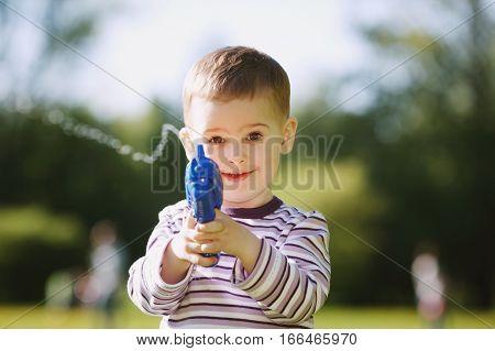 portrait of little boy with water gun