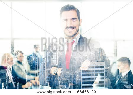 Successful team leader and business owner proudly standing with arms crossed in front of office window with New York city panorama reflection in glass. Employees working at office in background.