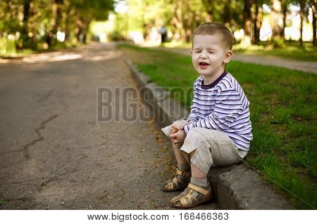 little funny boy squints sitting on the curb