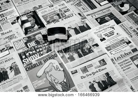 PARIS FRANCE - JAN 21 2017: Virtual Reality Mask above major international newspaper journalism Financial Times featuring headlines with Donald Trump America First at inauguration as the 45th President of the United States in Washington D.C