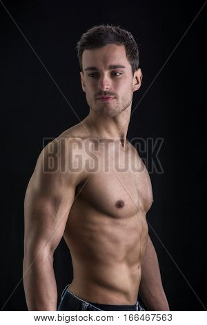 Handsome shirtless muscular man's profile, looking away, isolated on black