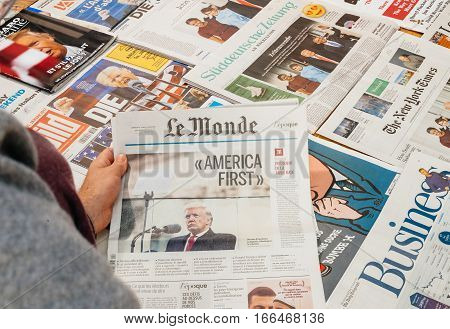PARIS FRANCE - JAN 21 2017: Man reading holding Le Monde above major international newspaper journalism featuring portrait of Donald Trump inauguration as the 45th President of the United States in Washington D.C