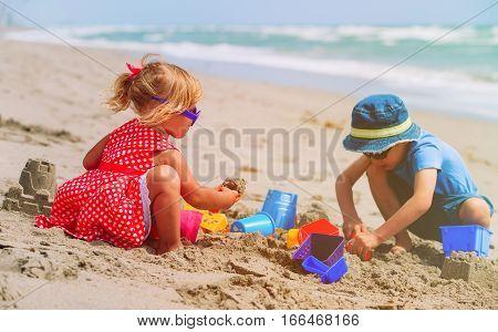 kids play with sand on summer beach, family beach vacation