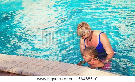 Grandmother teaching granddaughter to swim, active family