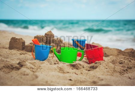 kids toys and sandcastle on beach, family at beach