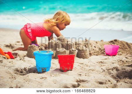 kids toys and little girl building sandcastle at beach, kids at beach